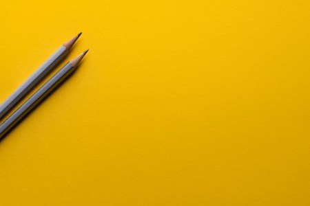 Pencils lie across a yellow background
