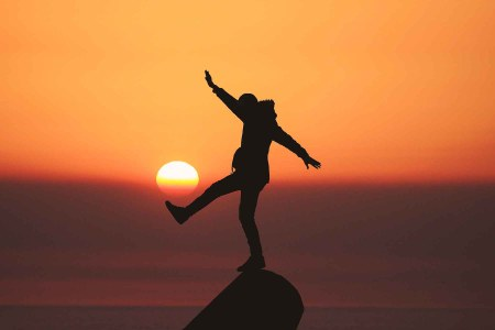 man balancing on rock at sunset