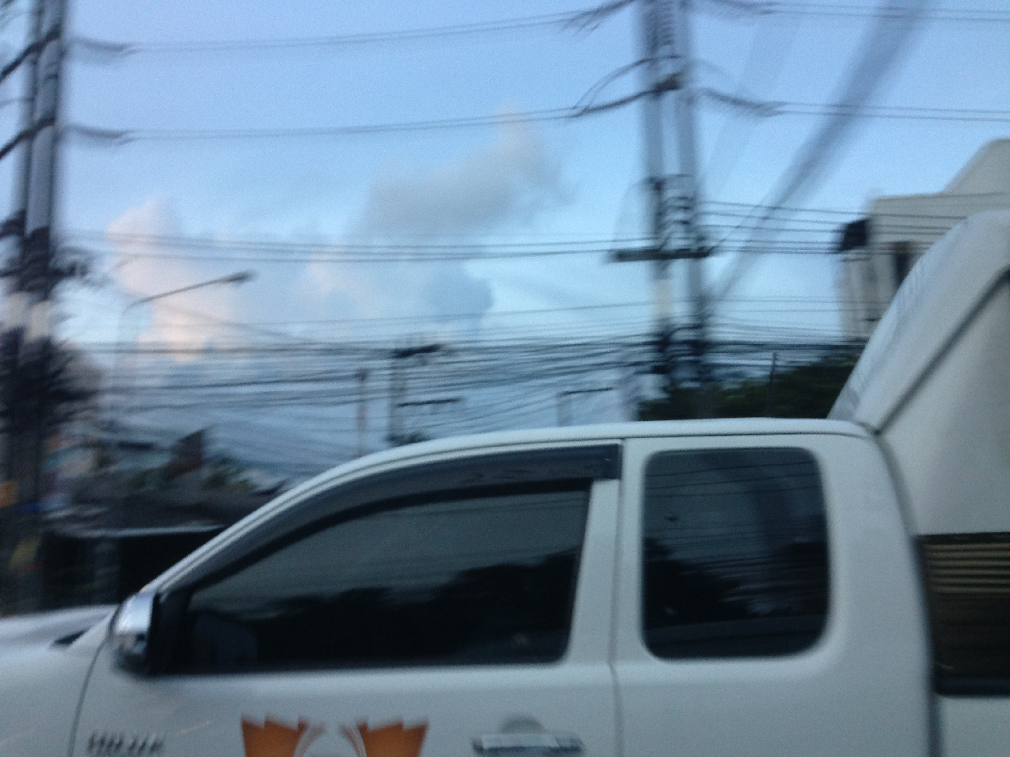 The front part of a white truck. Clouds and electricity poles and wires in the background.