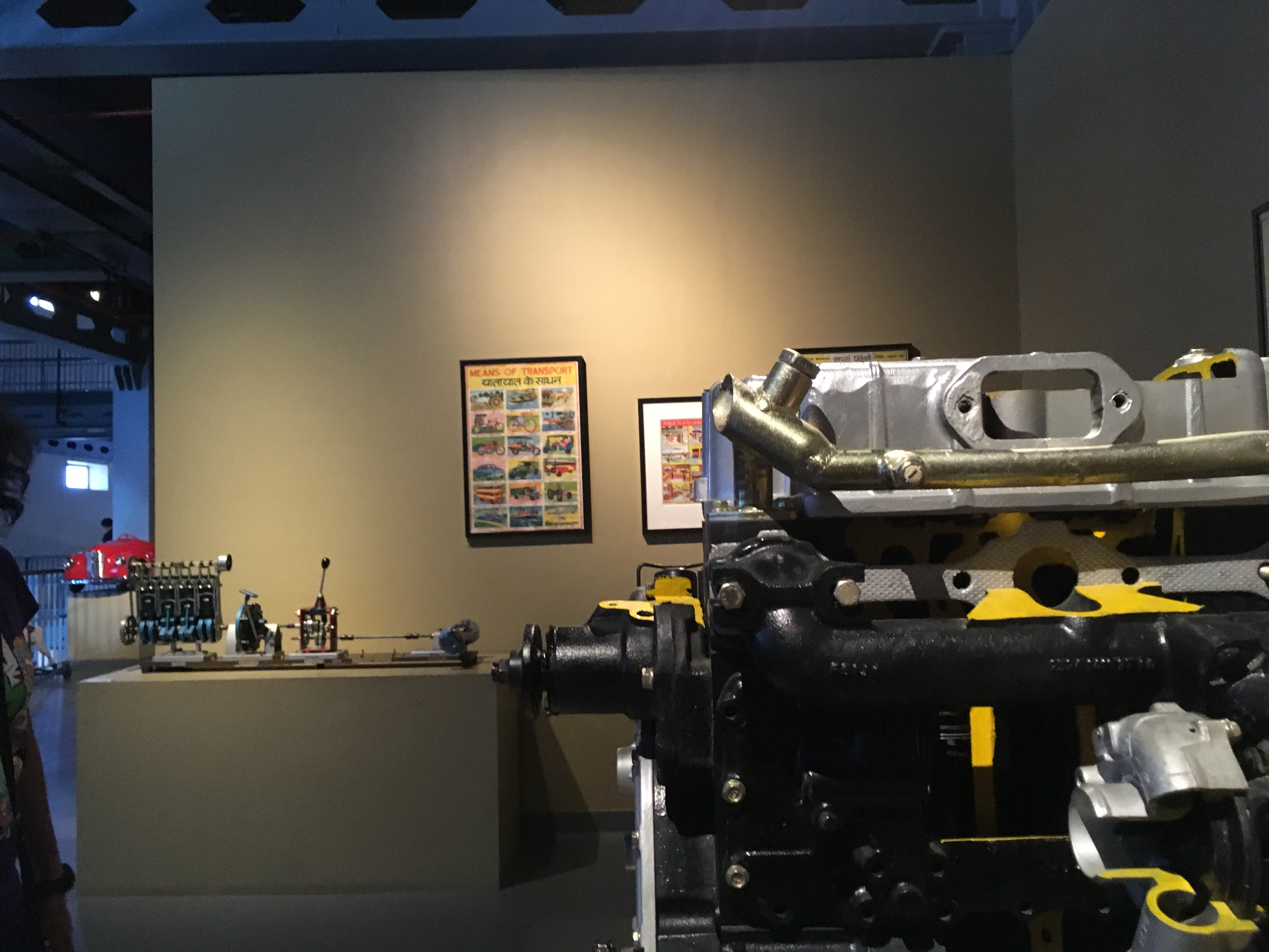 The working models of a diesel car engine on display with a petrol engine model in the background