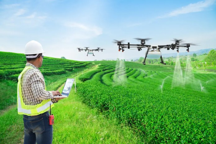 Technician farmer use wifi computer control agriculture drone fly to sprayed fertilizer on the green tea fields. Shutterstock.com / Suwin