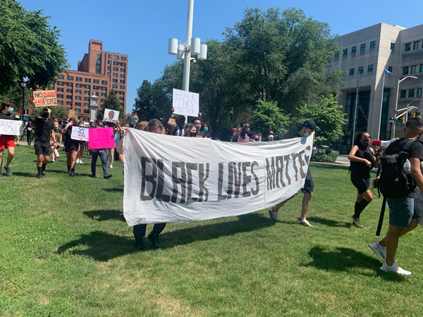 Picture of a protest. There is a white banner that says Black Lives Matter in painted all-caps black text.