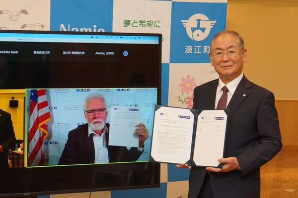 Namie, Japan, Mayor Yoshida holds a signed partnership declaration in person as Lancaster, CA, Mayor Parris holds the corresponding document online.