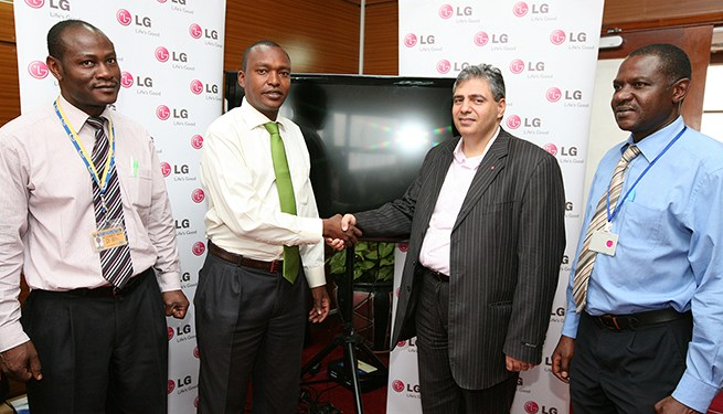 Alloys Siaya,  KAA ICT Services Manager (left) and Mr. Dominc Ngigi, KAA Corporate Affairs Manager (second left) receive ten LCD TVs from Mr. Moses Murji, LG East Africa Marketing General Manager (second right) as Eng. Owen Waithaka of KAA looks on.