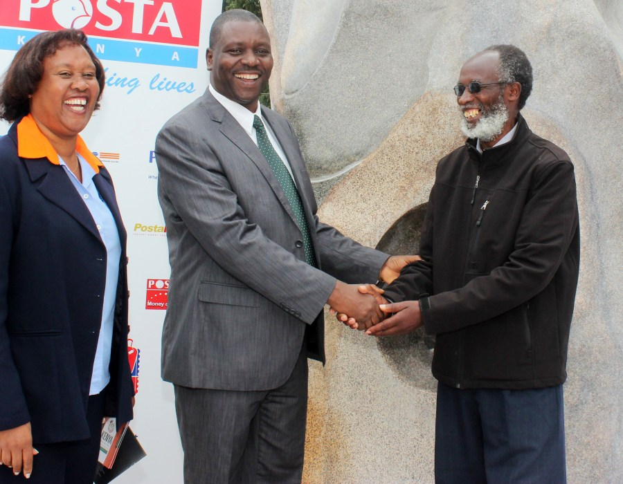 """Renowned sculptor, Elkana Onge'sa hands over the """"Hands Off Our Elephants"""" Sculpture to the Postmaster General, Dr. Enock Kinara for transportation to the Washington DC, U.S. by Posta for the Smithsonian Folklife Festival. Looking on is Elizabeth Mwaura, the General Manager, Courier Services at Posta."""