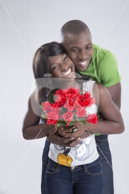 stock-photo-happy-romantic-couple-smiling-at-camera-holding-red-roses-18303