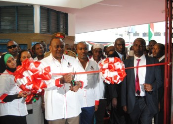 President Uhuru Kenyatta cuts the ribbon to officially open the Huduma Kenya Centre in Mombasa. With him is Mombasa County Governor Hassan Joho (Right) and Ministry of Devolution and Planning Cabinet Secretary, Anne Waiguru (Left and partly hidden
