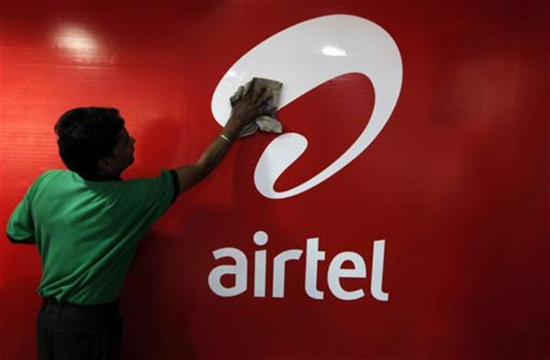A worker cleans a Bharti Airtel logo inside its shop in Kolkata