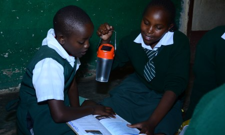Anne Mueni and Jane Ndunge of St. Mary's Tala Primary School use solar powered light to have an evening group discussion
