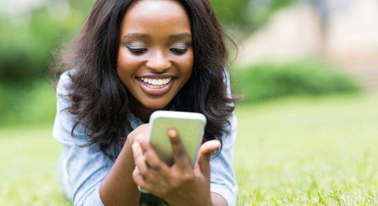 cheerful african american woman using smart phone