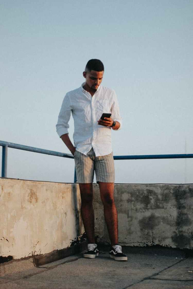 confident young african american male relaxing on terrace and using smartphone