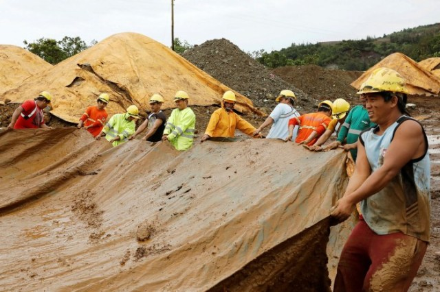 Workers at SR Metals cover a stockpile of nickel-ore minerals in Tubay, Agusan del Sur, in southern Philippines