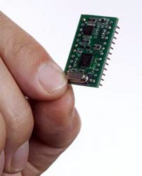 Fingers holding computer chip (PNNL)