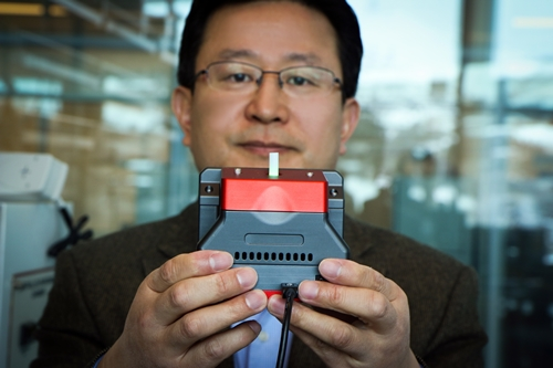 Ling Zang holds device