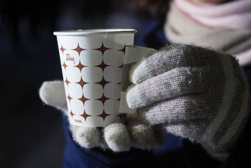 Hands in gloves holding coffee