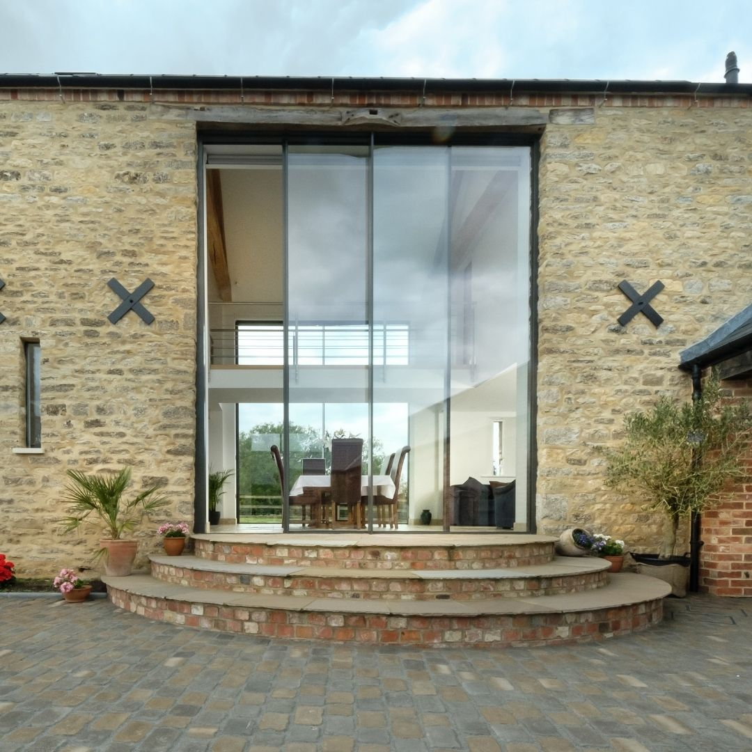 double height sliding glass doors in a contemporary barn conversion into a luxury home