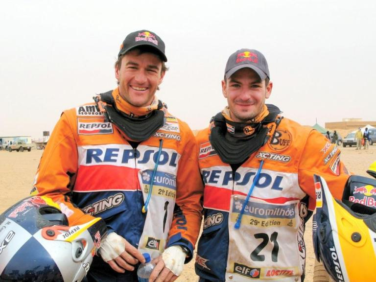 Frontal shot landscape photo of 2 motorcycle rallye bikers. It shows Marc Coma and Jordi Viladoms before the 6th etape of the 2007 Dakar Rally. They are both smiling into the camera. Interesting is the use of a High UV Buff® together with a neck brace. Look closer and you see the Buff® wrapping around the brace collar. That prevents rashes and keeps the sand out. It looks dusty and sandy in the background. Source: buff.eu Copyright: Distributed for the promotion of the High UV Buff® in motorcycle rallies