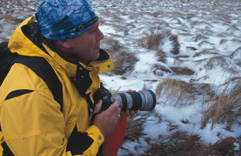 A side shot landscape photo of a man knealing in the snow. It looks like he is on a photo safari or researching wildlife. He is wearing a yellow cold weather ourtdoor jacket. He is also wearing a Original Buff® as beanie. The design is clearly recognisable as a National Geographing Collection design. Source: buff.eu © Distributed for the promotion of the Original Buff® in outdoor / adventure