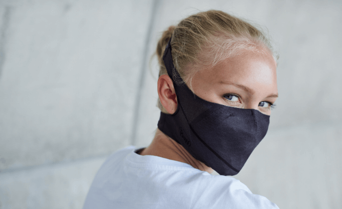 A woman in her 20's wearing a BUFF® Filter Face Mask and looking in the camera. You can see how the face mask perfectly fits the contour of her face. Source: buff.eu