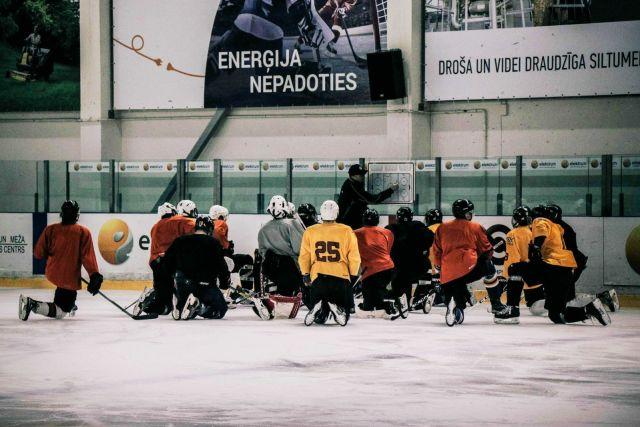 Un coach explique un exercicre à son équipe de hockey - Photo d'Arthur Edelman via Unsplash