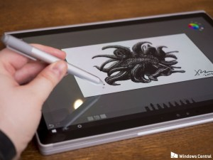Microsoft Surface laptop on a wooden surface with a black and white illustration and a hand holding the Surface Pen.