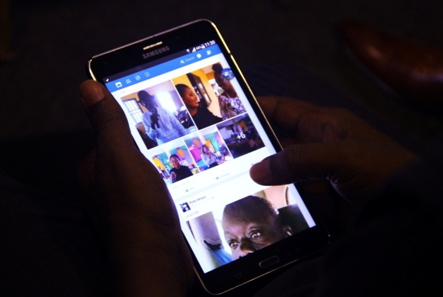 A mobile phone user looking at the screen of his smartphone