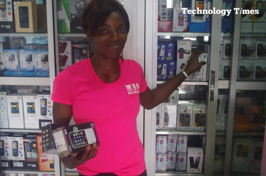 Technology Times file photo shows a lady showing off mobile phones at a mobile phone retail outlet in Computer Village, Ikeja, Lagos.