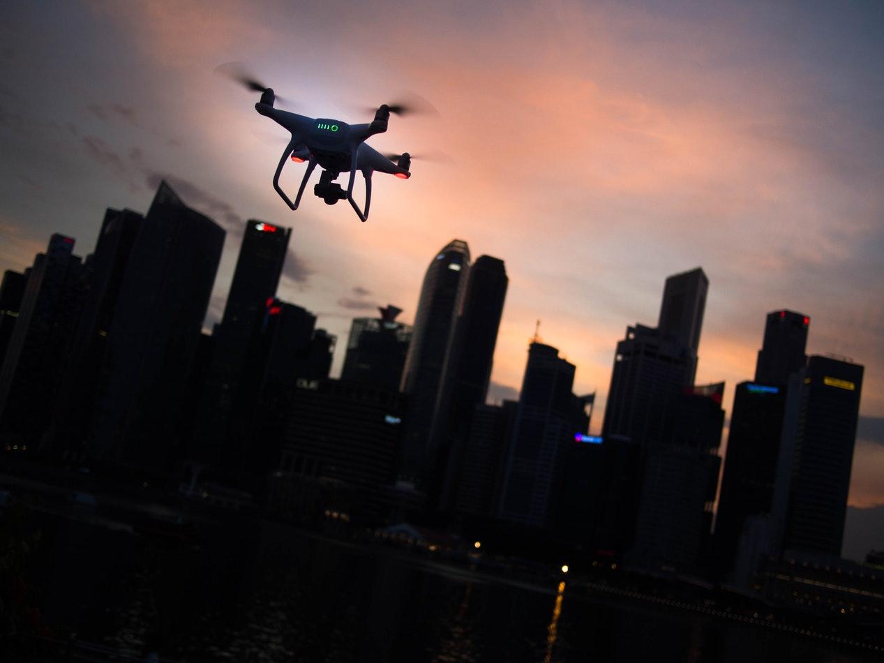 Un drone volant au-dessus d'un ville à la nuit tombée