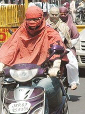 Women wearing scarf while riding her scootiy