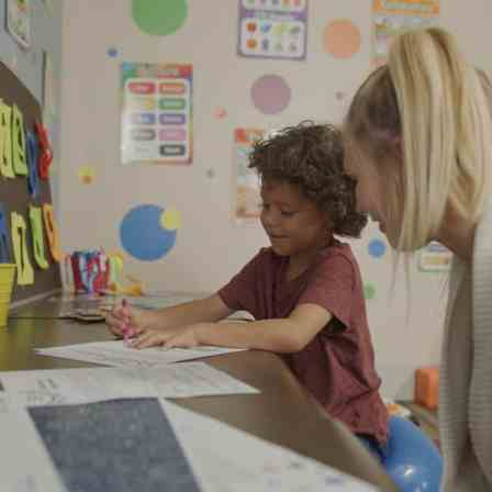 woman helping a child at a school desk