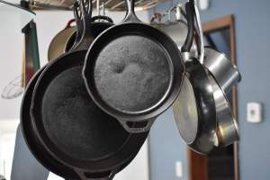 cast iron skillets hanging from a rack