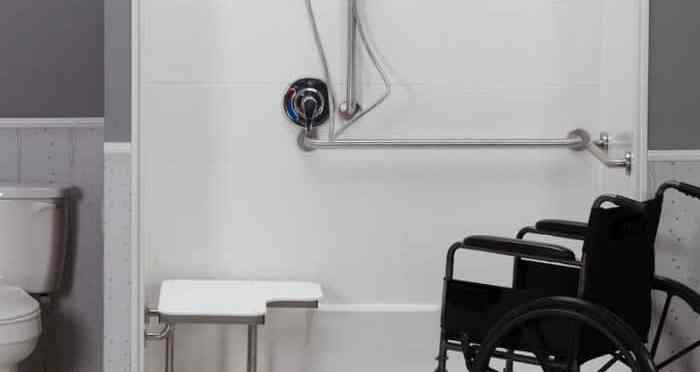 Wheelchair next to an open shower stall with a bench and handheld nozzle.