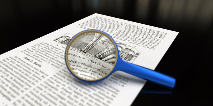Round magnifying glass over a newspaper.