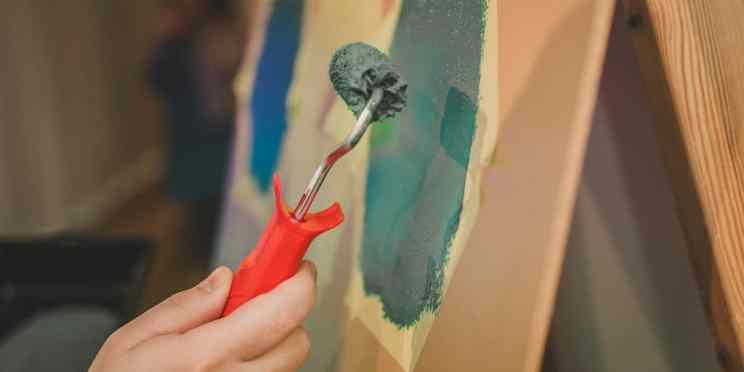 Close up of a hand holding a paint roller over colorful canvas.
