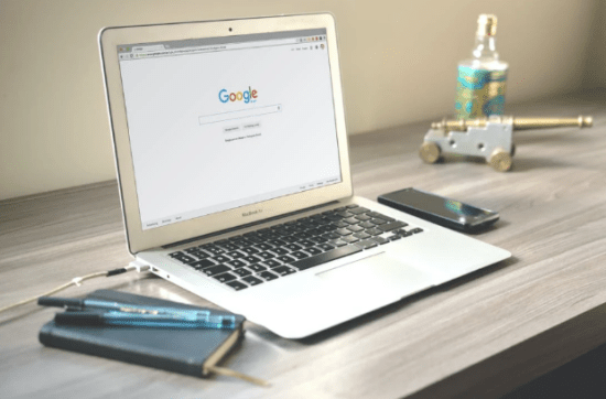 A silver laptop on a table with Google open to find websites that have benefited from Web SEO services