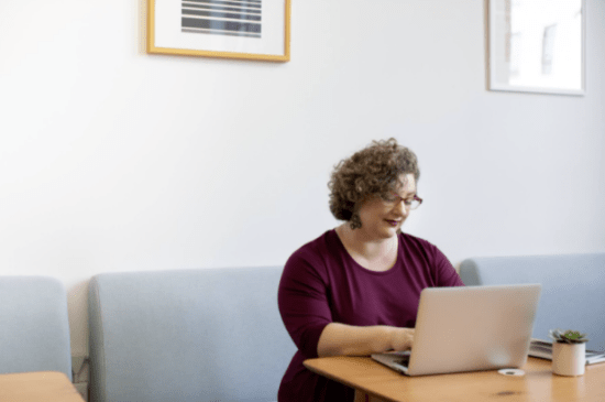 woman sitting down and working on her laptop