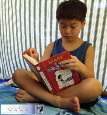 Boy reading in the summer.