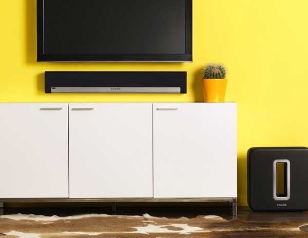 Sonos Playbar lifestyle shot, wall-mounted, with Sonos Sub speaker