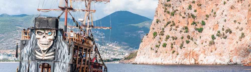 pirate ship sailing near rocky cliff