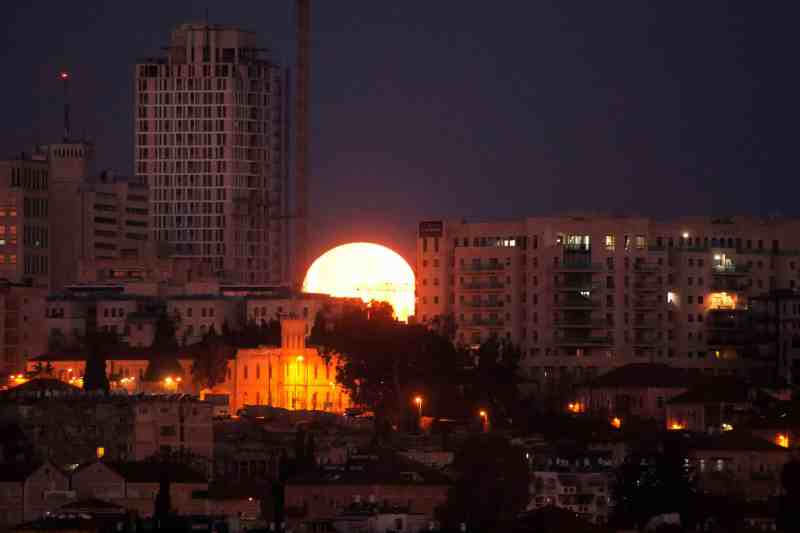 An unusual shot of the moon appearing wedged between buildings in Jerusalem, Israel Photograph: Menahem Kahana/AFP/Getty Images