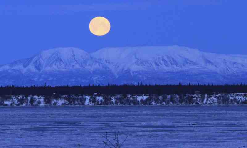The moon sets over Mount Susitna, known locally as Sleeping Lady, across Cook Inlet in Anchorage, Alaska. Super Blue Blood Moon Tech Urdu