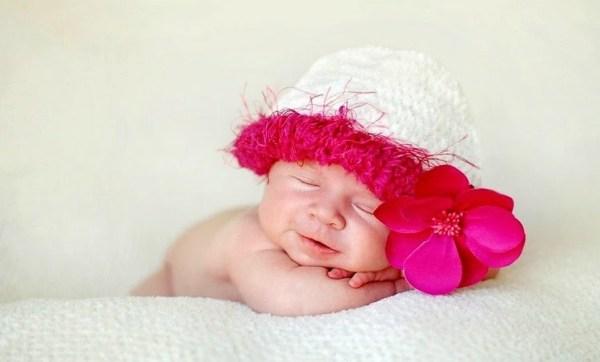 Bebê fofa com uma flor