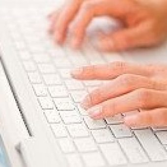 Woman typing on laptop keyboard, close-up of hands