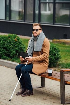 Homem sentado no banco da praça com sua BrailleOne ao lado sua bengala