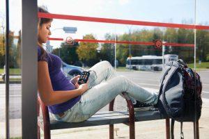 Jovem no ponto de ônibus com fone de ouvidos e o seu Victor Reader Stream