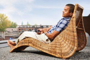 Homem sentado de forma relaxada na espreguiçadeira ouvindo seu Victor Reader Stream