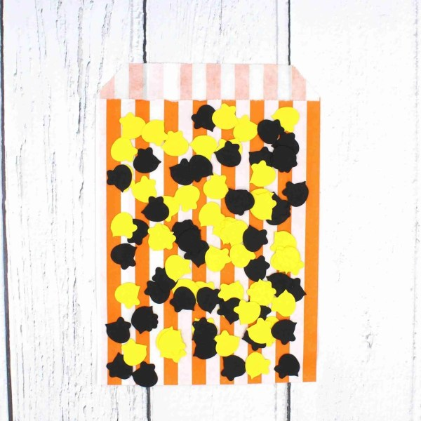 Yellow and black bee confetti for bee pun greetings card lay on top of orange and white striped bag