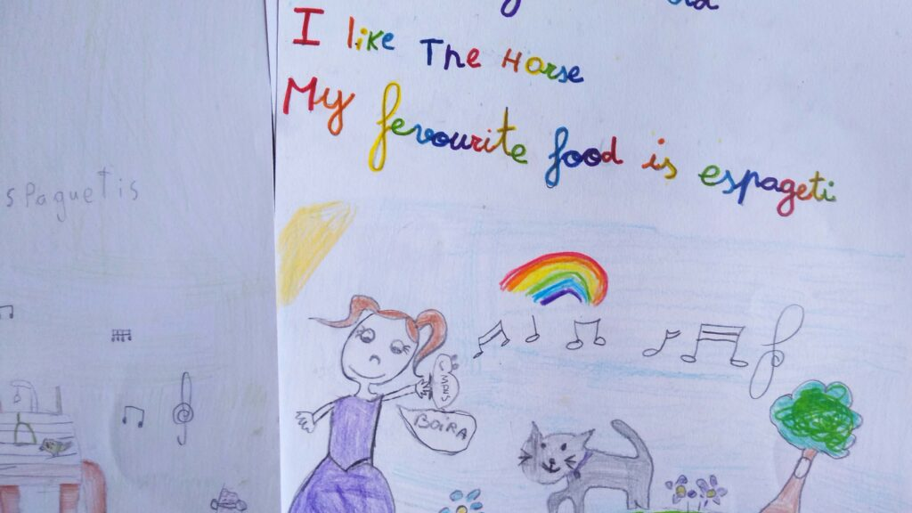 A child's drawing of a girl and a kitten and a rainbow with text reading 'my favourite food is espageti'