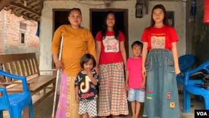 Rasminah (kiri) bersama empat dari lima anaknya di depan rumah mereka di Indramayu, Jawa Barat, Minggu, 7 Maret 2021.