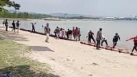 Terlihat secara bergerbolan, para ssnior memukul mahasiswa baru yang dijejerkan di atas pasir